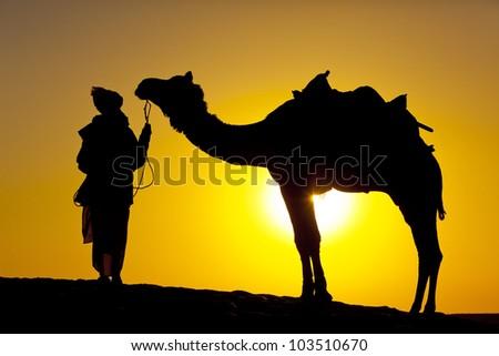 Rajasathan village man holds his camel, silhouette Sam dunes, Jaisalmer - India