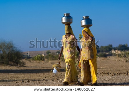 RAJASTHAN, INDIA - FEB 27: women lugging a water pot on their head on February 27, 2013 in Rajasthan, India. Due to the lack of piped water, poor tribals have to fetch water from its natural sources.