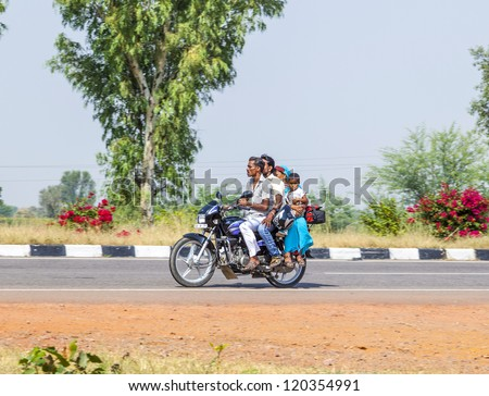 RAJASTHAN - INDIA - OCTOBER 18: Mother, father and small child ride on scooter on the highway on October 28, 2012 in Rajasthan, India. Up to six family members manage to ride these two wheelers.