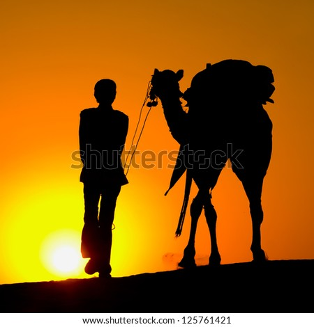 Rajasthan village. Silhouette of a man and camel at sunset in the desert, Jaisalmer - India