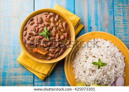 Rajma Or Razma is a popular North Indian Food, consisting of cooked red kidney beans in a thick gravy with spices. Served in bowl with Jeera Rise & green salad, isolated over colourful /wooden table. #425073301