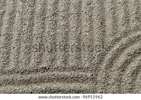 Raked sand detail representing waves on the sea in Zen garden
