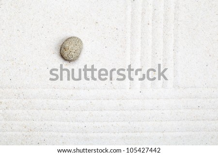 Raked sand garden with pebble - zen or meditation concept