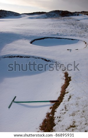 rakes in bunkers on a snow covered links golf course in ireland in snowy winter weather