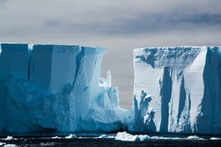 Raking light on a blue white floating tabular iceberg in the Weddell Sea off the coast of Antarctica with moody grey sky