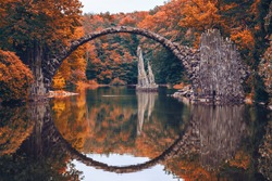 Rakotz Bridge (Rakotzbrucke, Devil's Bridge) in Kromlau, Saxony, Germany. Colorful autumn, reflection of the bridge in the water create a full circle