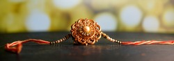 Raksha Bandhan background with an elegant Rakhi. A traditional Indian wrist band which is a symbol of love between Brothers and Sisters
