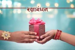 raksha bandhan (rakhi, rakshabandhan) concept, Indian brother giving gift to his sister, Raksha Bandhan Hindi calligraphy and Marathi calligraphy which reads as ' Raksha bandhan