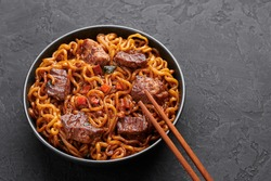 Ram-Don or Chapaguri noodles with beef steak in black bowl on dark slate background. Jjapaguri is a popular south korean dish with ramen and udon noodles and beef steak. Copy Space