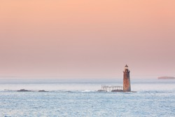 Ram Island Ledge Lighthouse at sunset, Portland Maine. The light is a lighthouse in Casco Bay, Maine, United States, marking the northern end of the main channel leading the harbor of Portland, Maine.