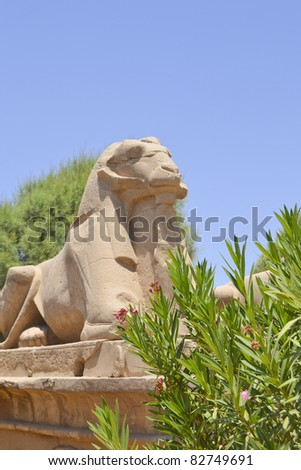 Ram sphinx next to a bush at the entrance to the Temple of Karnak in Luxor