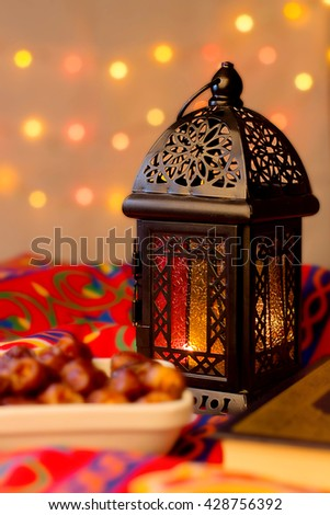 Ramadan Background - Lantern, dish of dates and Quraan on Ramadan colorful fabrics