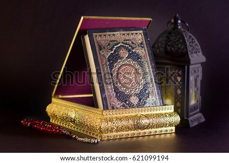 Ramadan Background - The Holy Quraan in golden box with Ramadan Lantern and red rosay on black background