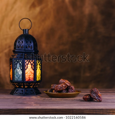 Ramadan concept. Dates close-up in the foreground. On the distant plan a blurry Ramadan Lantern on a wooden table. Textured yellow wall background. Space for text on the right. Square 1:1 frame.  #1022160586