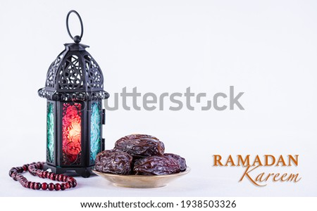 Ramadan food and drinks concept. Ramadan arabian lamp, wood rosary, and dates fruit on white background.