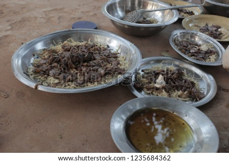ramadan food: many silver bowls full of pasta and chicken with fried onions, outdoors on a sunny summer day in the Gambia, Africa
