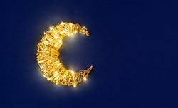 Ramadan glowing crescent on blue background