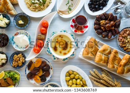 Ramadan,iftar,beginning meal before main menu with traditional soup,date fruits,olives,Ramadan bread,water walnut on the blue table with other foods.Special design,top view.