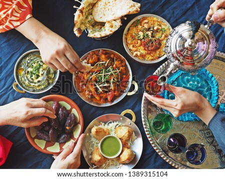 Ramadan iftar meal theme people eating variety foods together on dining table with large dates (Medjool), Samosas, Aloo Gobi, Chicken Biryani, Moroccan tea set, Palak Paneer and Naan bread. (top view)