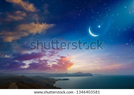 Ramadan Kareem background, rising crescent and stars above dark mountains and serene sea. Elements of this image furnished by NASA #1346403581