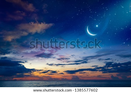 Ramadan Kareem background with crescent, stars and glowing clouds above serene sea.  Elements of this image furnished by NASA #1385577602