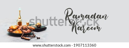 Ramadan kareem concept with dates and holy book of muslims and rosary, siwak, perfume on  gray background