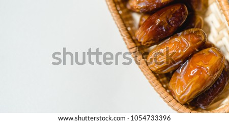Ramadan kareem food concept with premium Dried date in a wooden basket on white background. #1054733396