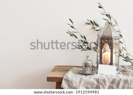 Ramadan Kareem greeting card, invitation mockup. Silver lantern with burning candle and silver cup with tea or coffee. Green olive tree branches on old wooden table background. Muslim Iftar dinner.