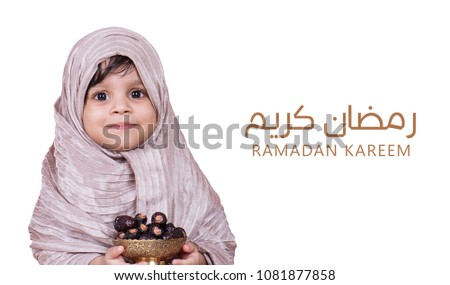 Ramadan kareem meaning Blessed ramadan with two year old cute baby holding bowl of dates fruit #1081877858