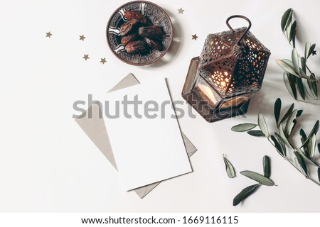 Ramadan Kareem mockup. Bronze plate with dates fruit, olive branches, glowing Moroccan lanternand blank greeting card on white marble table. Iftar dinner. Eid ul Adha background. Flat lay, top view.