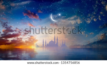 Ramadan Kareem religious background with mosque silhouettes reflected in serene sea, rising crescent and stars. Elements of this image furnished by NASA. Mixed media image. #1354756856