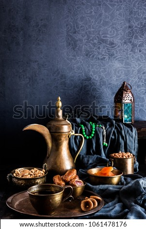 Ramadan kareem with premium dates,nuts and arabic coffee. Festive still life with oriental ramadan lantern and iftar food concept.