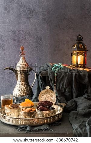 Ramadan kareem with premium dates,nuts and arabic tea. Festive still life with oriental ramadan lantern and iftar food concept.
