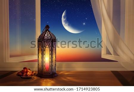 Ramadan lantern by the open window. Beautiful Greeting Card with copy space for Ramadan and Muslim Holidays. An illuminated Arabic lamp. Mixed media.