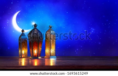 Ramadan lanterns on the table with moon on dark blue background. Beautiful Greeting Card with copy space for Muslim Holidays. An illuminated Arabic lamp. Mixed media.