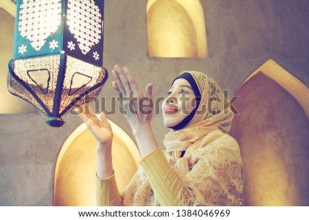 Ramadan Mubarak theme Muslim woman in yellow traditional Muslim clothing preparing the lantern for the month of fasting. People with worldwide symbol represents the holy month. (selective focus) #1384046969