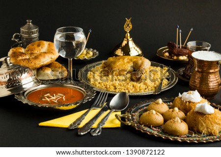 Ramadan Table with tomato soup,chicken hips on rice,buttermilk,Ramadan bread,date fruits and Turkish pastry dessert on the black surface.Used stylish copper and silver kitchen utensil.