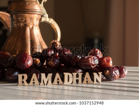 RAMADHAN text with dates fruit and arabic brass teapot on wooden table top.  #1037152948