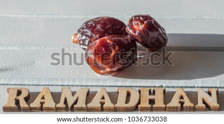 RAMADHAN text with dates fruit on wooden table top. #1036733038