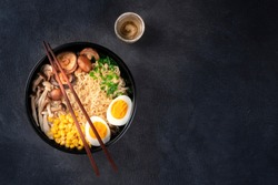 Ramen. Soba noodles soup with an egg, shiitake and enoki mushrooms, corn and scallions, shot from the top on a dark background with chopsticks, sake, and copyspace
