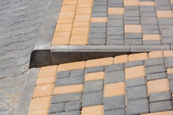 Ramp for the descent of wheeled vehicles from the pedestrian sidewalk onto the road paved with stone tiles with a barrier border, closeup side view nobody.