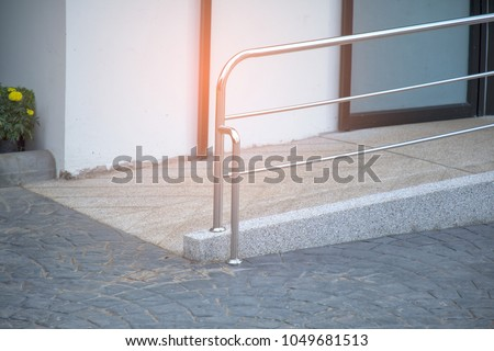 Ramp way with stainless steel handrail for support wheelchair disabled people infront of the disable toilet.  Foto stock ©