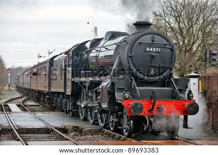 RAMSBOTTOM, ENGLAND - JANUARY 23: A Black 5 steam locomotive passes over a manual level crossing into Ramsbottom station during the East Lancashire Railway Steam gala on January 23, 2011 at Ramsbottom, England.