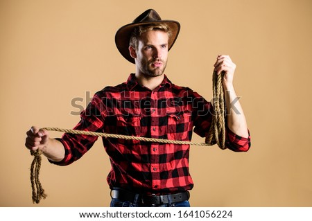 Ranch occupations. Lasso is used in rodeos part competitive events. Lasso can be tied or wrapped. Western life. Man cowboy beige background. Man wearing hat hold rope. Lasso tool of American cowboy. ストックフォト ©