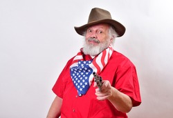 Rancher is pointing his pistol right at the camera. Angry man looking serious, wearing a patriotic bandana and point his gun right at the camera.