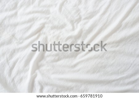 Random abstract pattern of a white crumpled bed sheet in a hotel room. The manufacturing of bedsheet uses cotton, cotton blends, polyester and others fibers such as linen, silk modal and bamboo rayon.
