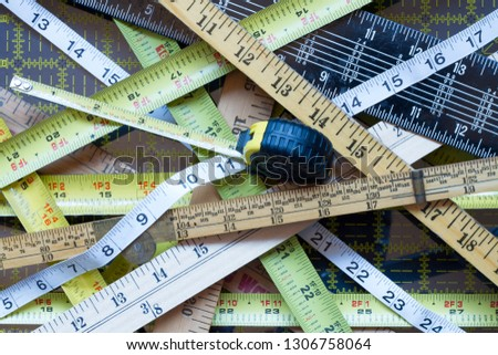 Random collection of Crisscrossed tape measures and yard sticks #1306758064
