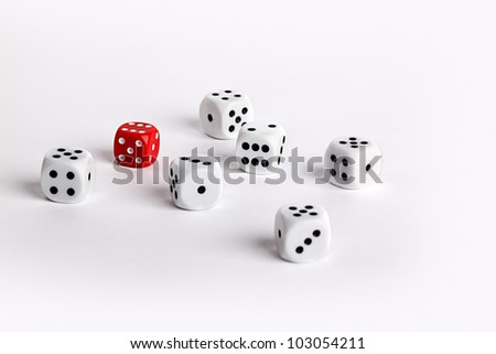 Randomly scattered white dice with one red dice conceptual of individuality
