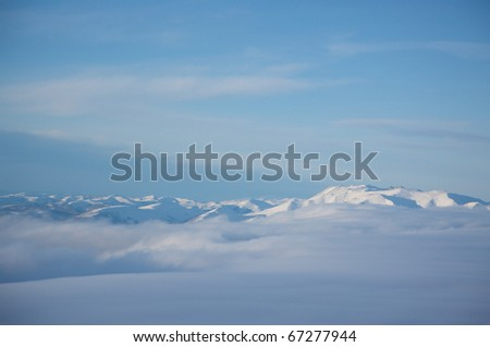 Range of snowcapped mountains peaking through a cover of clouds in Alaska.