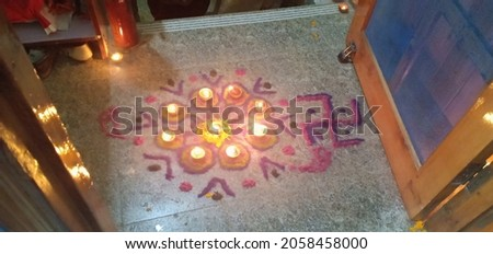 Rangoli on the occasion of Diwali as it features a Diya as the main attraction.Shubh Labh is made on the entrance of home.